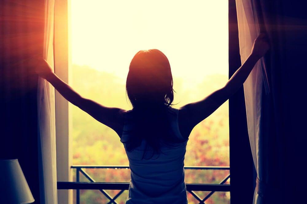 Mujer abriendo las cortinas