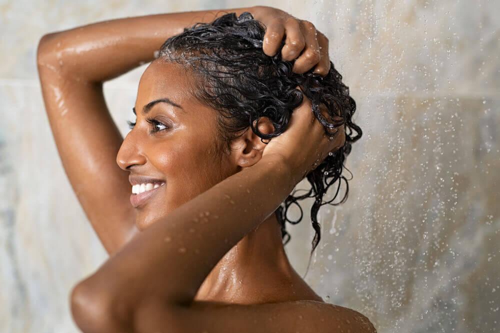 Mujer aplicándose champú en la ducha.