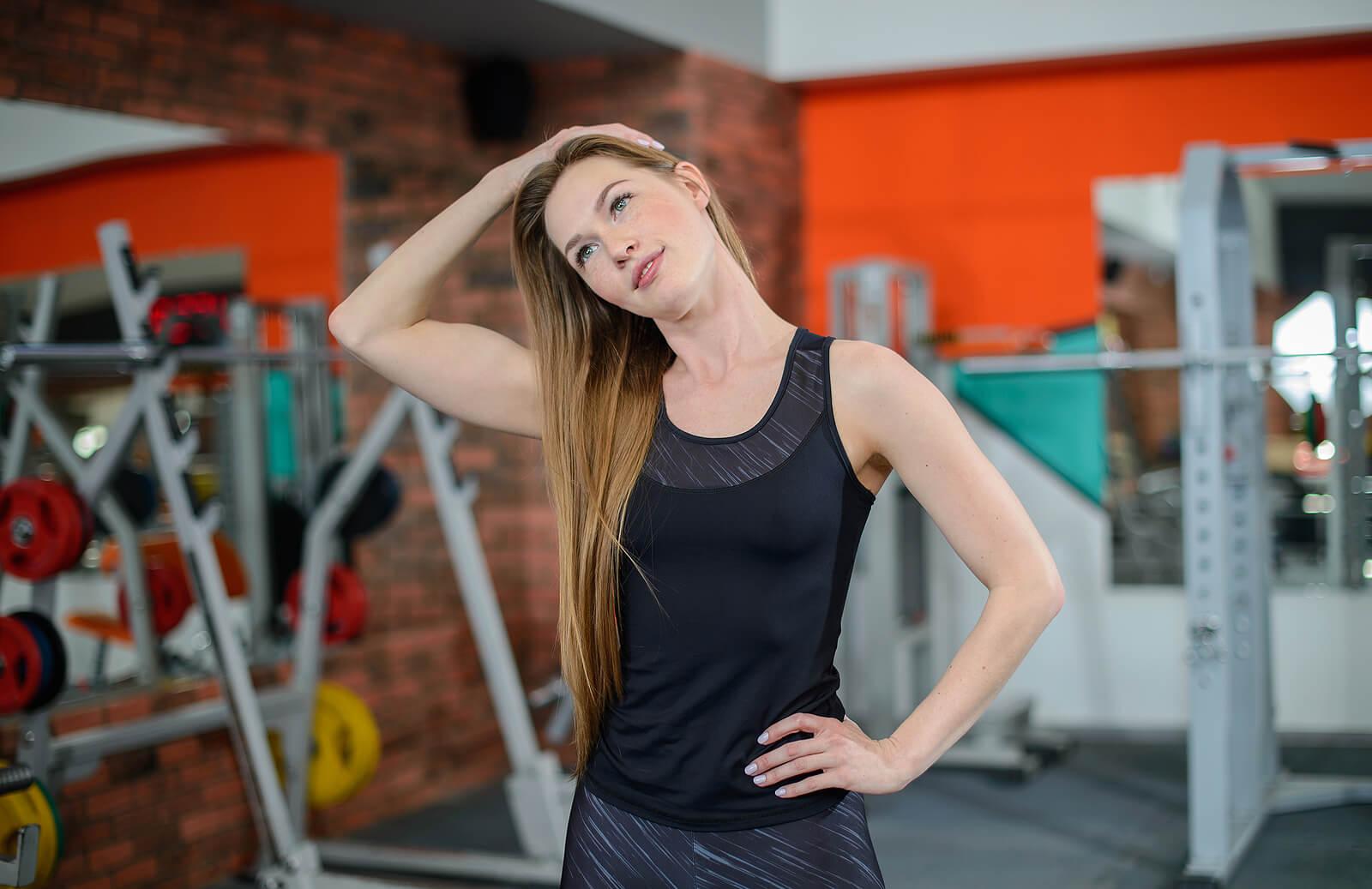 Mujer en el gimnasio haciendo ejercicio para el cuello