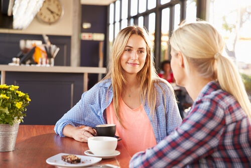 Dos mujeres hablando mientras toman café.