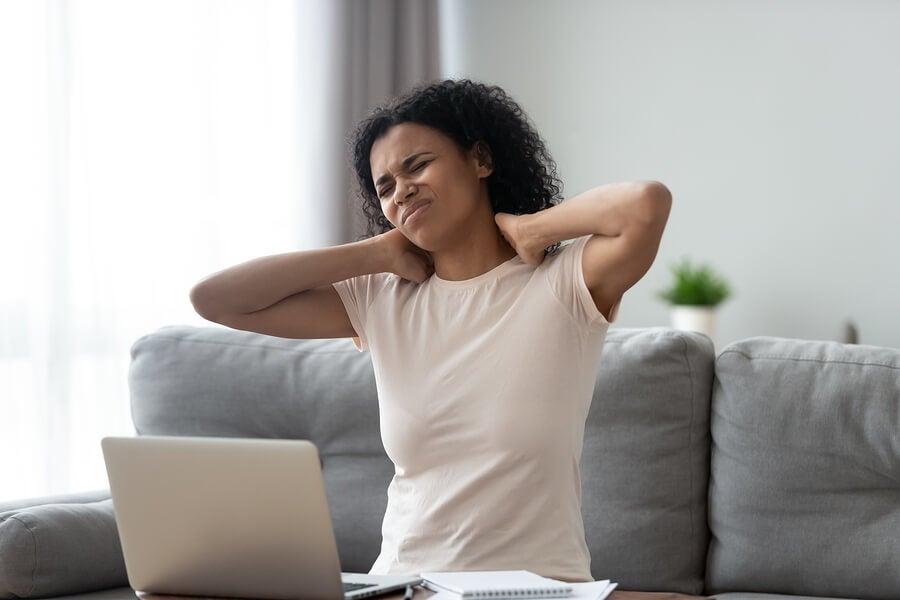 Chica con dolor de cuello por usar mucho la laptop.