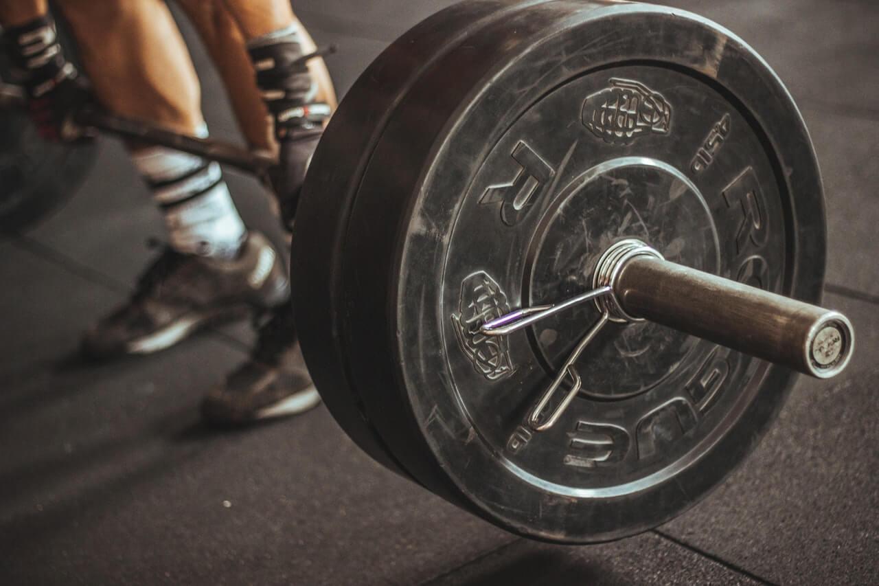 Hombre levantando pesas para trabajar el bodybuilding.