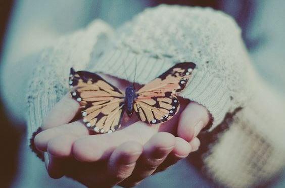 Mano con mariposa representando el arte de ignorar y dejar ir