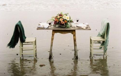 Mesa en la playa con sillas vacías.