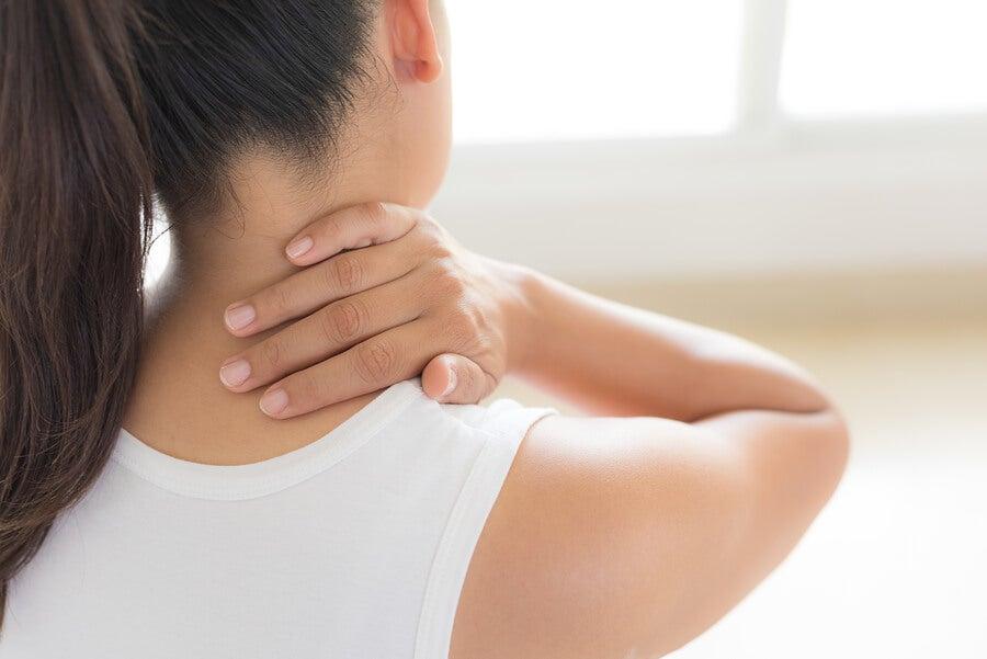 Mujer de espaldas con dolor de cuello.