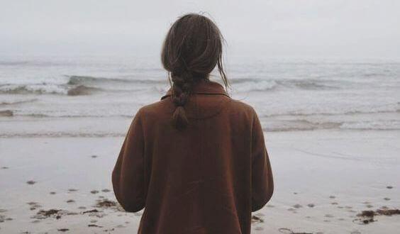 Mujer de espaldas en una playa en invierno.