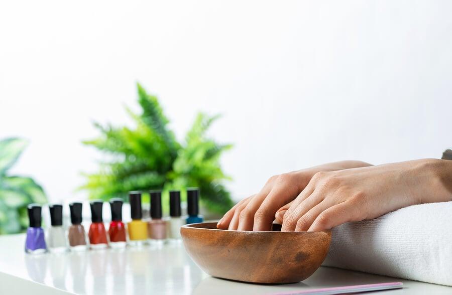 Manos con agua fría para secar rápido la pintura de uñas.