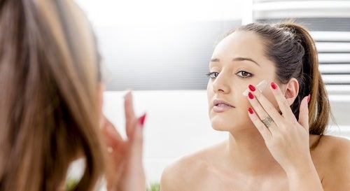 Mujer exfoliándose la cara para prevenir el envejecimiento prematuro