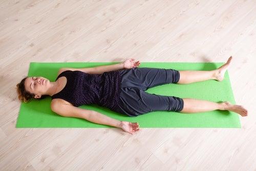 Mujer tendida en el suelo haciendo respiración consciente