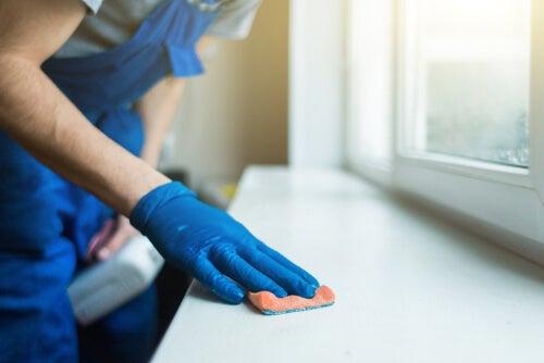 Hombre limpiando superficie con jabón desinfectante.
