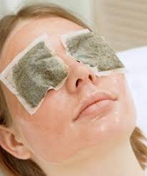Mujer con bolsas de manzanilla en los ojos.