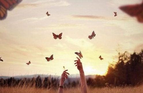 Manos alcanzando mariposas