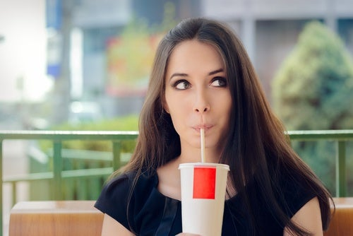 Woman drinking a soda to illustarte decisions that could increase our biological age