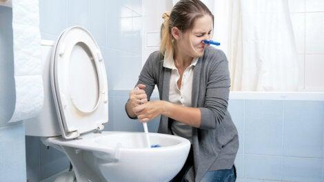 Mujer limpiando inodoro con mal olor.
