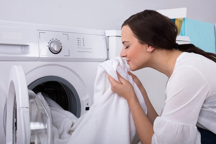 Mujer oliendo toallas limpias con suavizante natural.