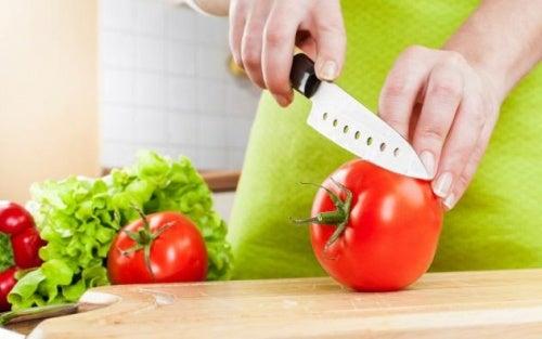 Persona cortando un tomate con un cuchillo nuevo y afilado