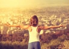 Mujer-con-los-brazos-abiertos-subida-en-una-montaña