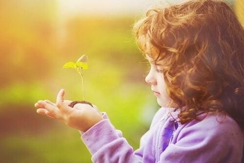 Niña observando el crecimiento de una planta en sus manos