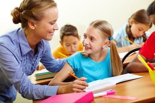 Profesora-ayudando-a-su-alumna-en-clase-con-las-tareas