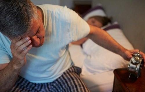 Hombre en la cama mirando el despertador.