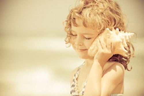 A child listening to a shell.