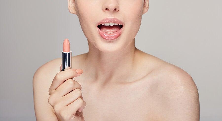 Mujer sujetando pintalabios en tono nude.