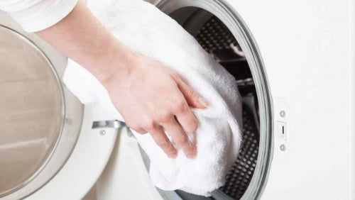 A person putting a towel in a washing machine.