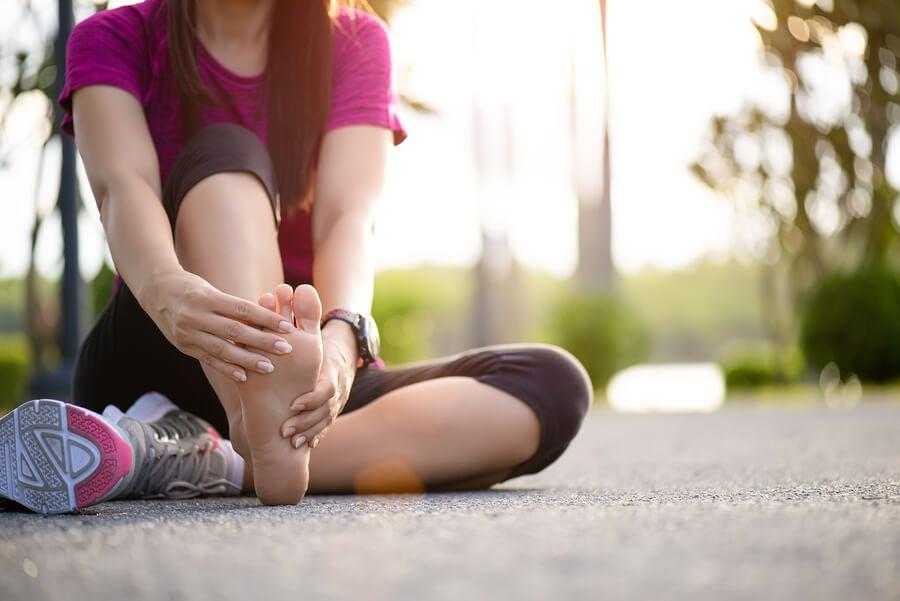 Mujer con un calambre en la pierna por correr sin calentar.