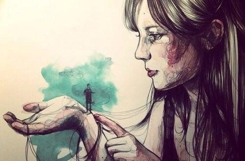 Mujer con hombre diminuto en la mano