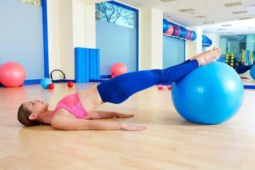 Chica apoyando las piernas estiradas sobre una pelota suiza en el gimnasio