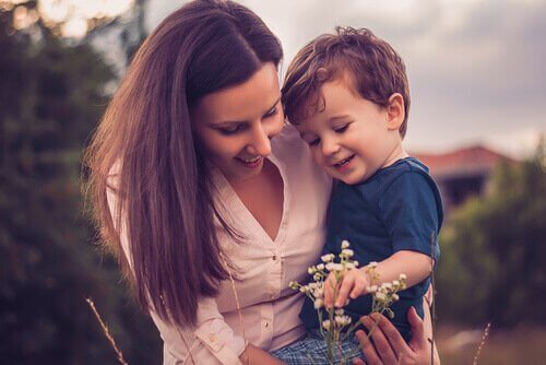Súper mamá-cogiendo-a-su-hijo-en-brazos-mientras-ven-una-flor