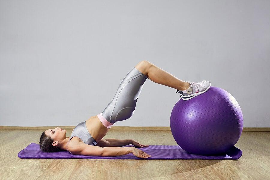 Chica haciendo pilates con un balón suizo