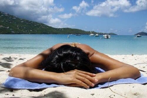 Mujer en la playa tomando el sol a punto de sufrir una insolación
