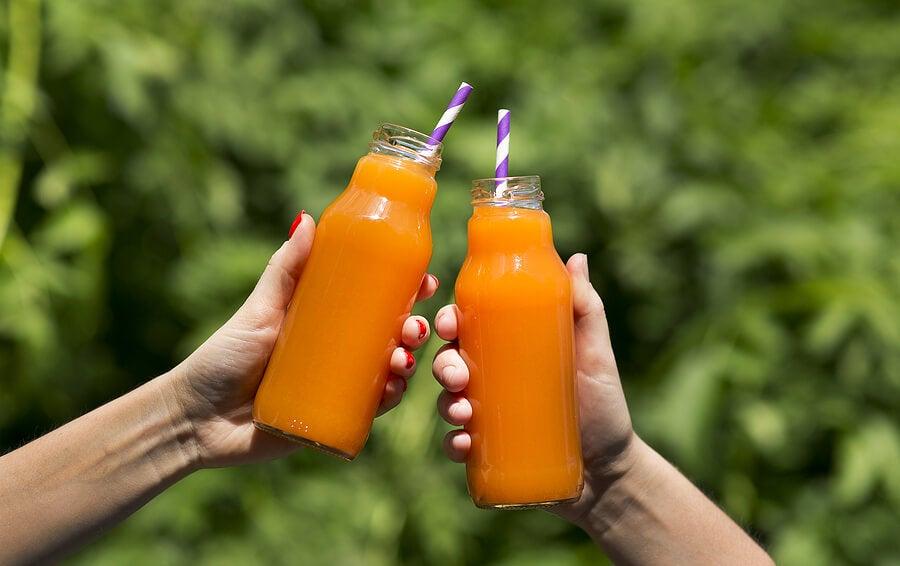 Manos sosteniendo botellas de zumo de zanahoria.