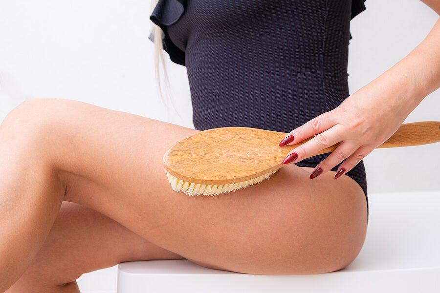 Mujer haciéndose un cepillado en seco en las piernas.