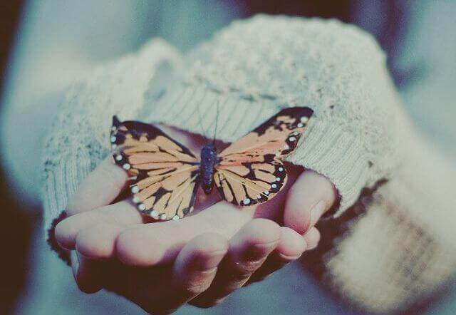 A lady with a butterfly in her hand.