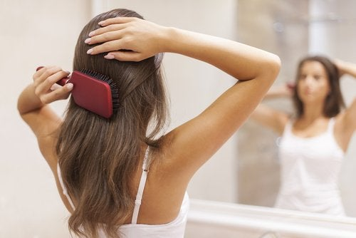A woman brushing her hair in front of the mirror.