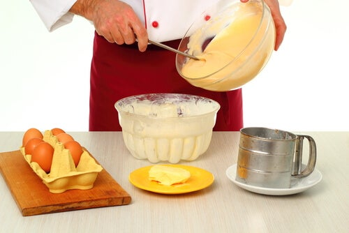 Cocinero batiendo crema en un bol con demás ingredientes para elaborarla en la mesa.