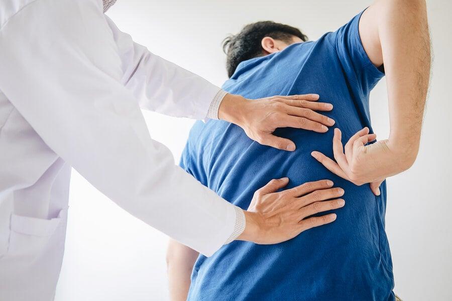 Fisioterapeuta examinando los los dolores del nervio ciático.