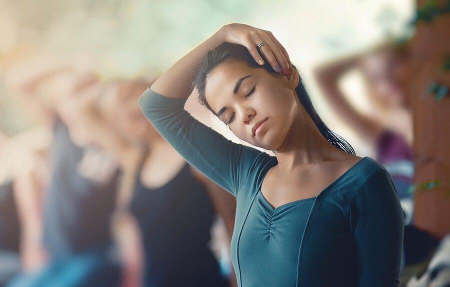 Chica realizando un estiramiento de cuello en clase de yoga.
