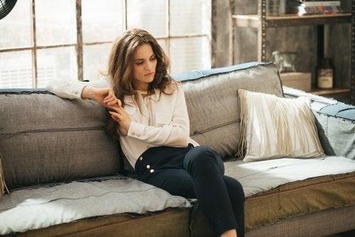 Mujer desganada en el sofá a causa de la anemia