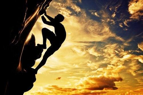 Hombre-subiendo-una-montaña simbolizando cuando buscas la felicidad