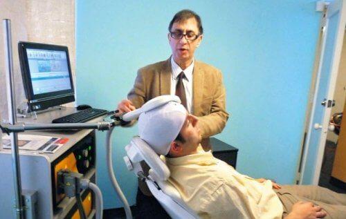 Psiquiatra colocando a su paciente el casco para tratar la depresión