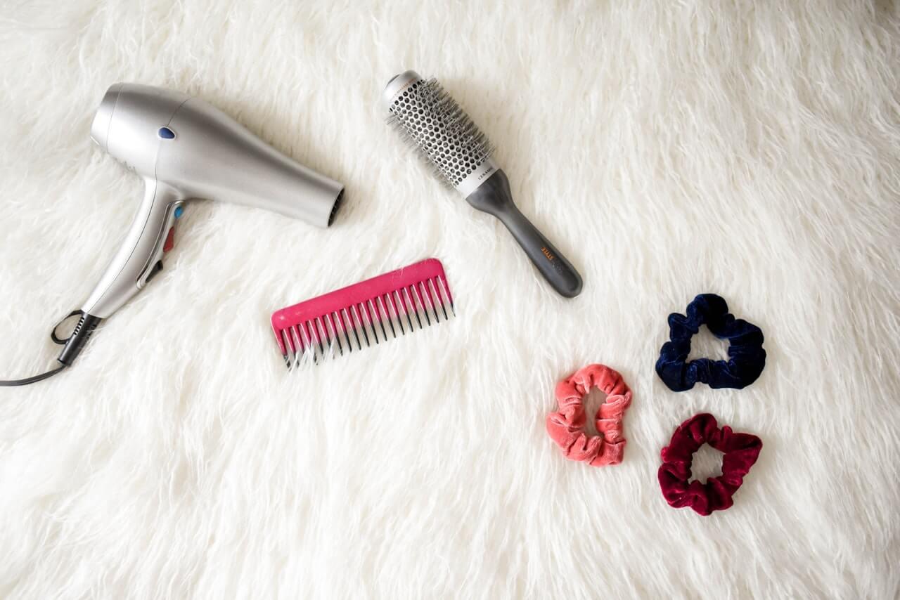 Secador de pelo, cepillo y coletas.