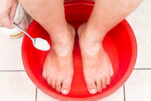 Someone with their feet in a bowl of the apple cider vinegar and baking soda remedy
