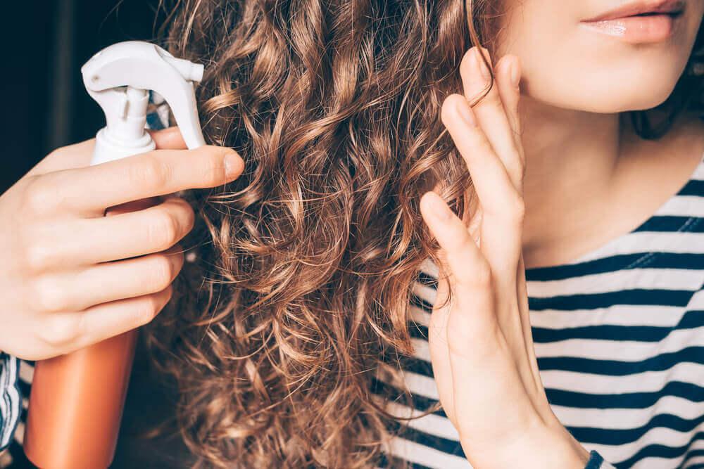 Chica aplicándose aceite de coco en el cabello.