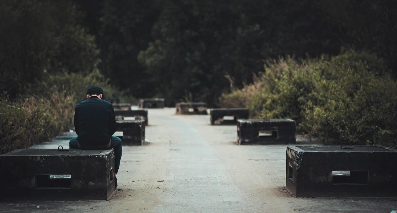 Hombre triste y solo sentado en un banco.