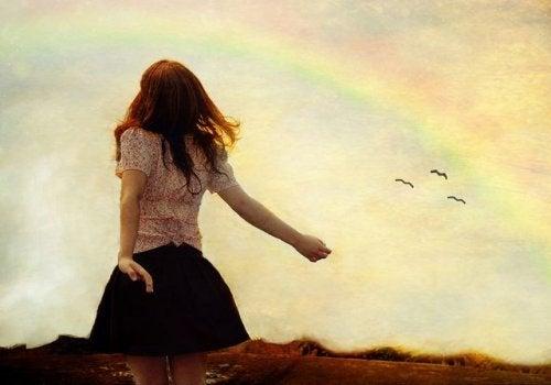 Mujer junto a arco iris, libre de quien la trata mal
