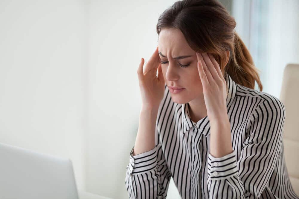 Mujer delante del ordenador con dolor de cabeza.