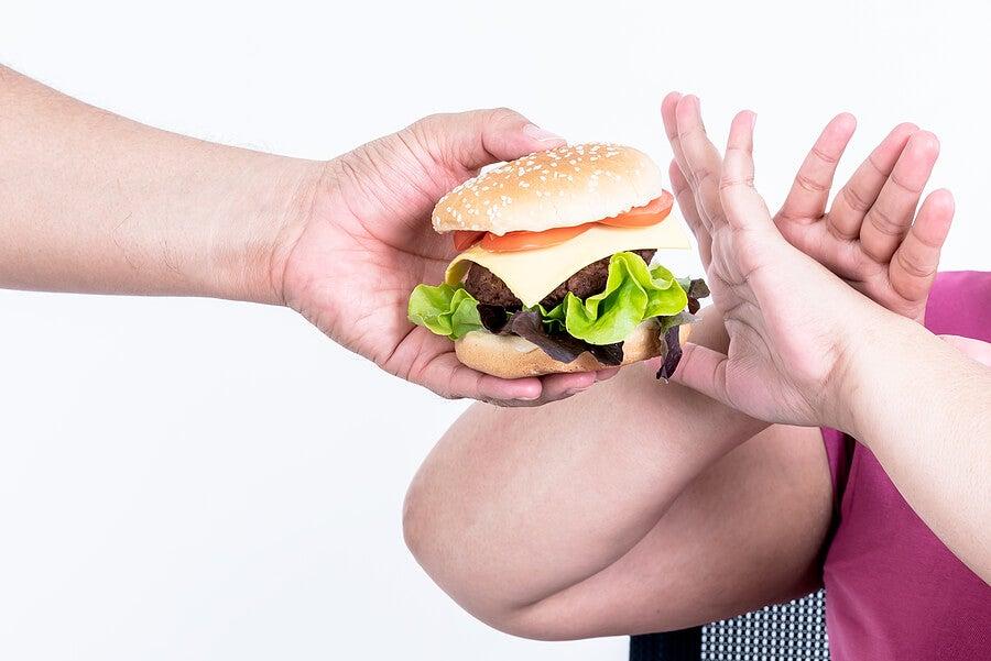 Persona obesa rechazando hamburguesa